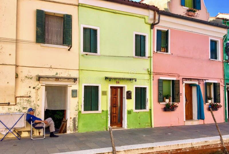 Widok few historyczni kolorowi domy z lokalnym mężczyzną siedzi na zewnątrz cieszyć się pięknego lato ranek w Burano, Włochy obraz royalty free