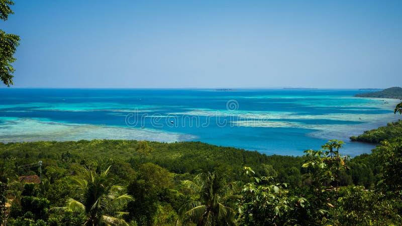 Widok górski z zieloną lasu i drzewa palmą z błękitnym morzem w odległości w karimun jawie zdjęcia stock