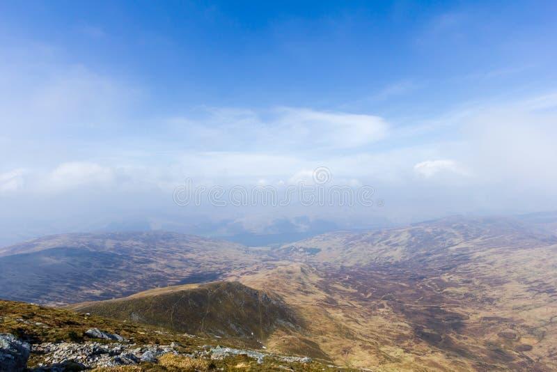 Widok halna dolina z skalistą ścieżką, trawą i jeziorem w tle pod, majestatycznym bielem i niebieskim niebem chmurnieje zdjęcia stock