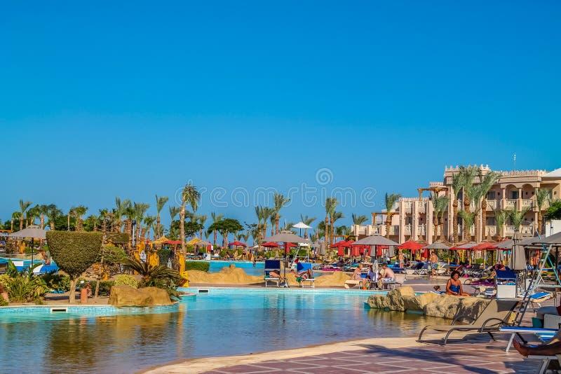 Widok hotel's rekreacyjny teren na plażowym i dennym brzeg, drzewka palmowe pod niebieskim niebem słoneczny dzień obraz stock