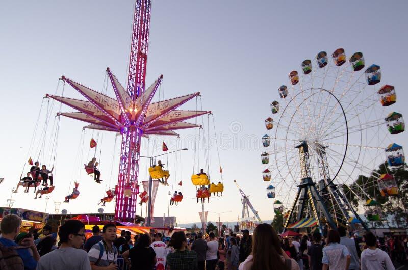 Widok Huśtawkowy przejażdżki wierza i Ferris koło przy Sydney Królewskim Wielkanocnym przedstawieniem w mrocznym czasie zdjęcia royalty free