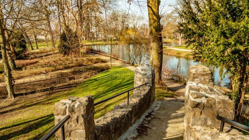 Widok kamienny footbridge w Proosdij parku z swój drzewami i stawem zdjęcie royalty free