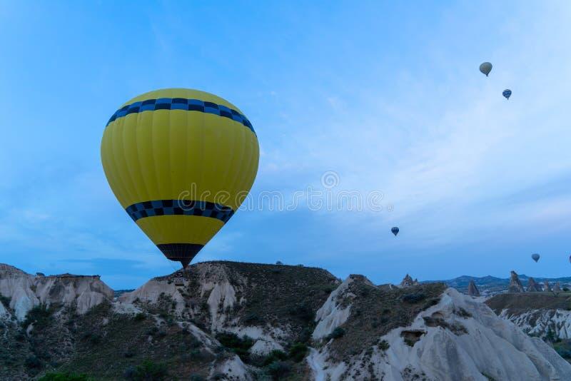Widok kolorowy koloru żółtego balon i balony lata nad Cappadocia góry krajobrazu unikalną ziemią w ranku zaświecamy zdjęcia stock