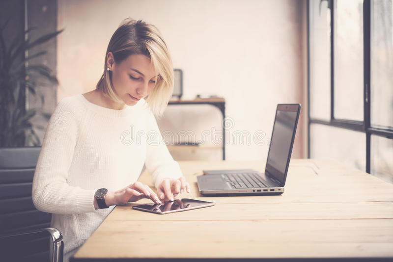 Widok młoda piękna kobieta pracuje przy drewnianym stołem Kobieta wręcza wzruszającą pastylkę na miejscu pracy Pojęcie biznes zdjęcia royalty free