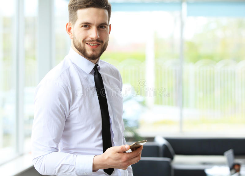 Widok Młody atrakcyjny biznesowy mężczyzna używa smartphone zdjęcie royalty free