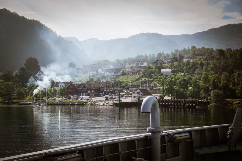 Widok mała norweska wioska od promu zakrywającego w mgle fotografia stock