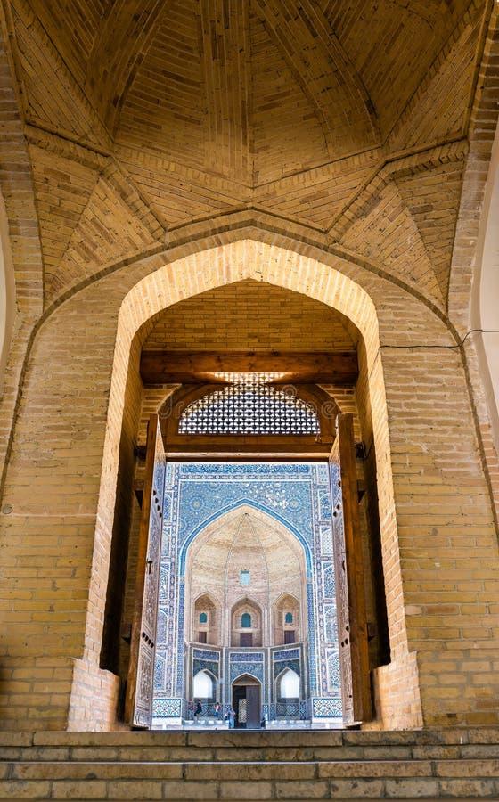 Widok Mir Madrasa przez drzwi Kalyan meczet w Bukhara arab, Uzbekistan obrazy royalty free