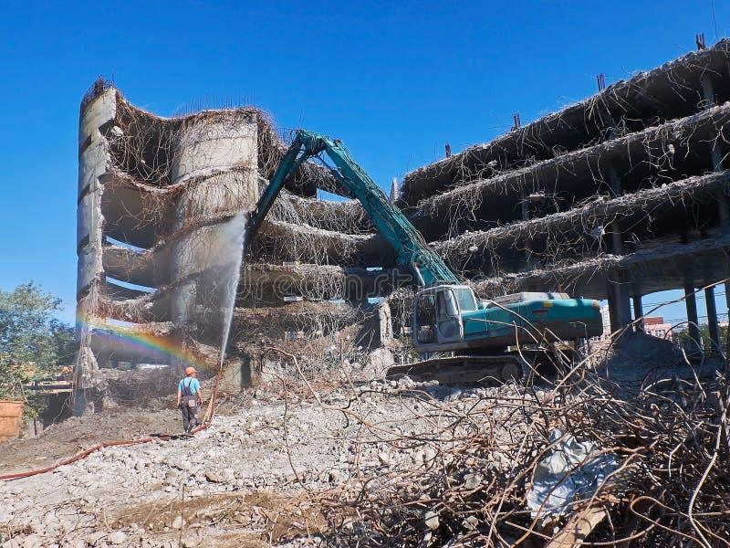 Widok na deconstruction pracach ciężkim pneumatycznym dźwigowym ekskawatorem z specjalnym wyposażeniem i pracownikiem z wodnym wę obraz stock