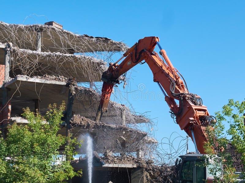 Widok na deconstruction pracuje ciężkim pneumatycznym dźwigowym ekskawatorem z specjalnym wyposażeniem Budynki i domu Przemysłowy zdjęcia stock