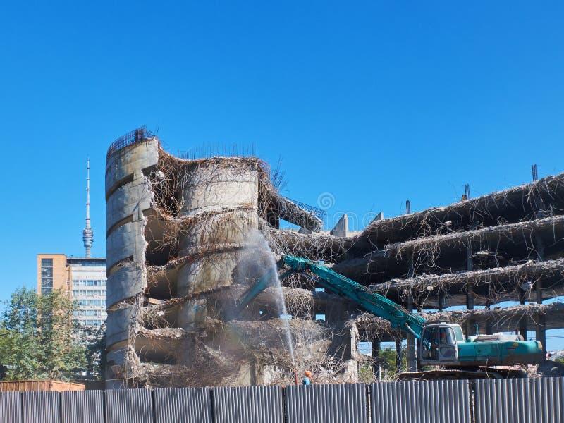 Widok na deconstruction pracuje ciężkim pneumatycznym dźwigowym ekskawatorem z specjalnym wyposażeniem Budynki i domu Przemysłowy zdjęcie royalty free