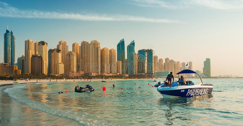 Widok na Dubaj Marina i Jumeirah wyrzucać na brzeg, dokąd ludzie są relaksujący i parasailing przy zmierzchem obrazy stock