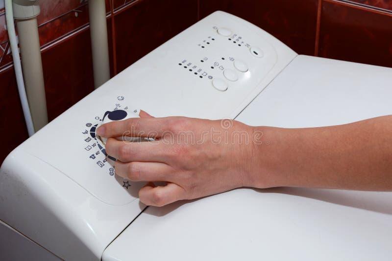 Widok na jak kobieta obraca dalej pralka Kobieta wybiera płuczkowego tryb na pralce fotografia royalty free