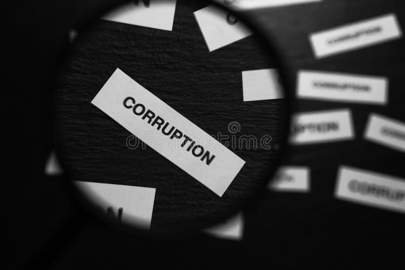 Widok na kawałek papieru z słowem korupcja przez magnifier szkła na czarnym tle zdjęcie stock