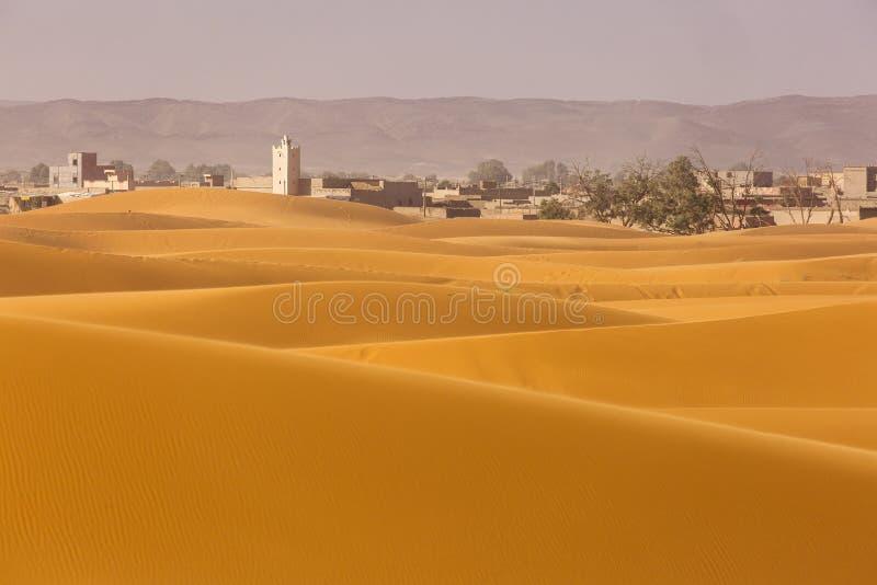 Widok na miasto Merzouga w tle na Saharze Pustynnej z pięknymi liniami i kolorami na wschodzie słońca Merzouga, Maroko obrazy stock