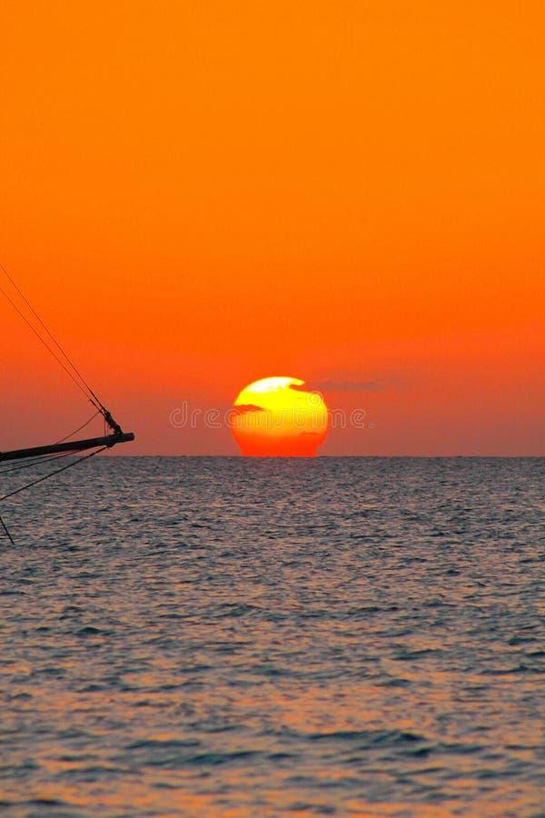 Widok na zmierzchu od karaibskiej plaży z pomarańczowej czerwieni rozjarzonym niebem i czarną sylwetką odosobniona żeglowanie łód zdjęcia stock