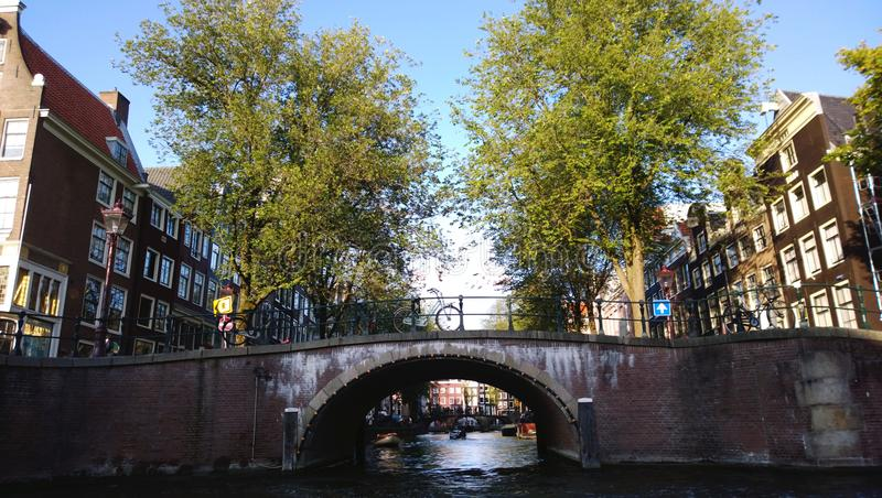 Widok nad kanałami Amsterdam podczas wodnego odprowadzenia - mosty, łodzie, budynek fasady, widok spod spodu obrazy stock