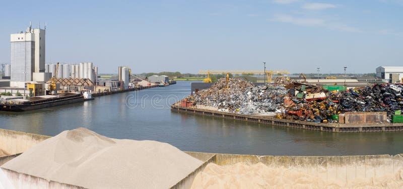 Widok nad kanałem w parku przemysłowym blisko Kampen holandie z fabrycznymi budynkami, stary żelazo, złomowi stosy piasek, składu obraz royalty free