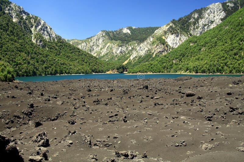 Widok nad powulkanicznymi popiółami na ustronnym błękitnym krateru jeziorze otaczającym górami w środkowym Chile przy Conguillio  zdjęcie stock