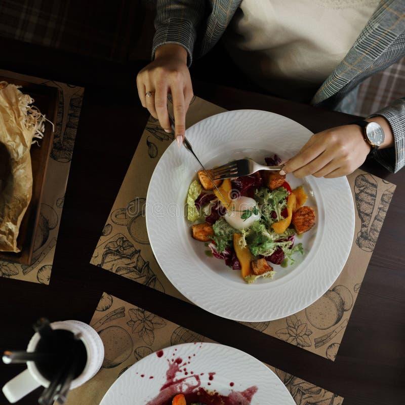 Widok nad rękami z sałatką i kłusującym jajkiem na białym talerzu cutlery i warzywa na stole indoors zdjęcia royalty free