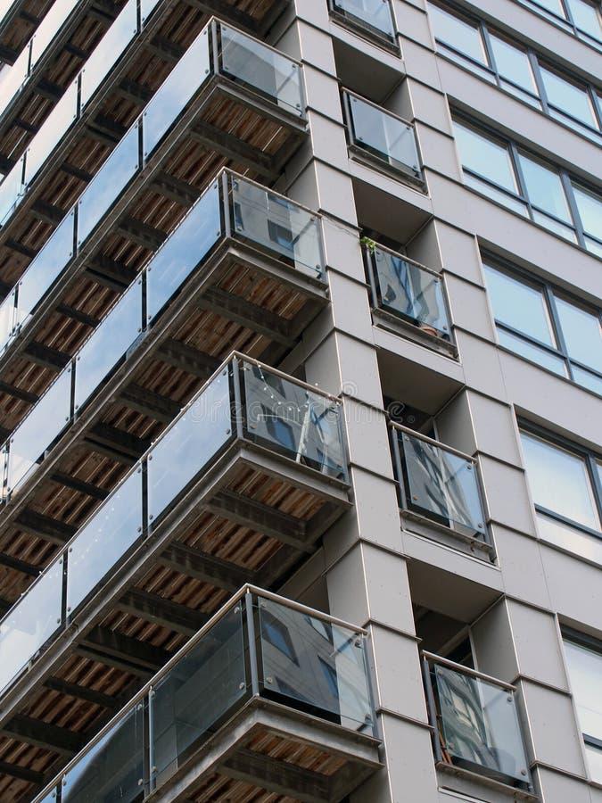 Widok narożników nowoczesnego budynku mieszkalnego z czarnymi okładzinami i szklanymi balkonami odbijającymi inne budynki fotografia royalty free
