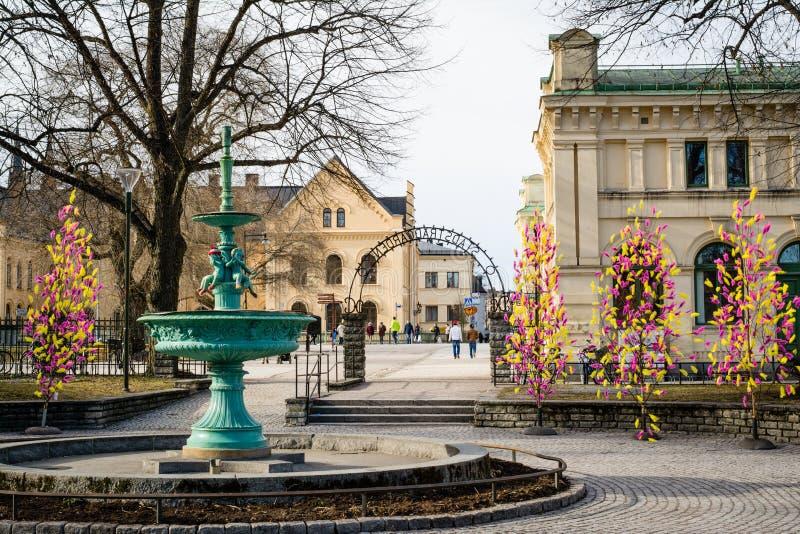 WIDOK nieaktywna fontanna z tradycyjnymi colourful piórkami na drzewach dla Wielkanocnego wystroju UPPSALA SZWECJA, Mar - 26, 201 obraz stock