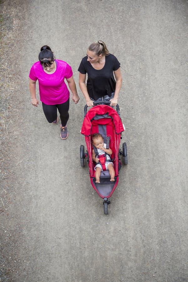 Widok od above Dwa kobiety chodzi wpólnie i opowiada na śladzie z wózkiem spacerowym obraz stock