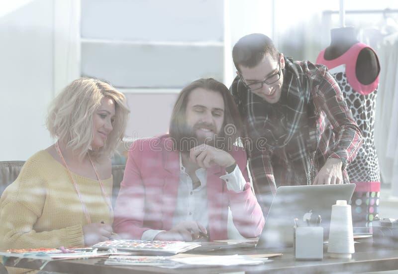 Widok od behind szkła trzy kolegi dyskutuje nowych pomysły w studiu obrazy royalty free