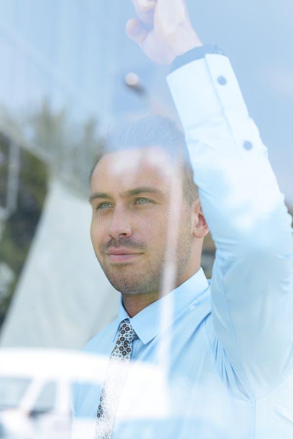 Widok od behind szkła ufny biznesmen przyglądający out okno jego biuro fotografia royalty free