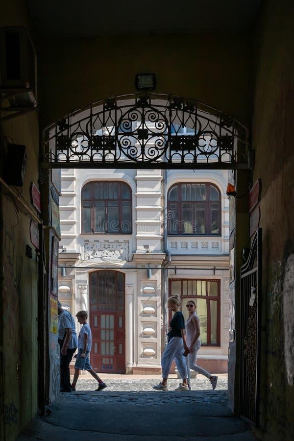 Widok od ciemnego łuku brama jaskrawa ulica Weekendowi świętowania obraz royalty free