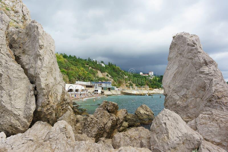 Widok od diwy skały plaża kurort wioska Ludzie sunbathe i pływają w morzu na chmurnym letnim dniu zdjęcie stock