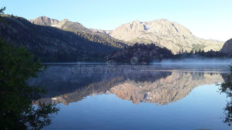 Widok od krzaków mountain& x27; s odbicie na spokojnym jeziorze z kayaking fotografia royalty free