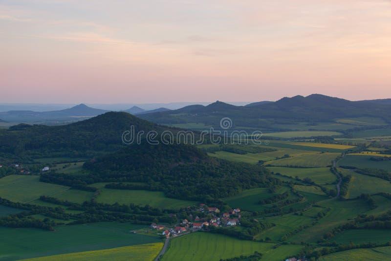 Widok od Lovos wzgórza na Velemin wiosce Zmierzch w ?rodkowych Artystycznych ?redniog?rzach, republika czech zdjęcia royalty free