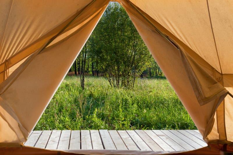 Widok od namiotu brezentowego na zieloną łąkę fotografia stock