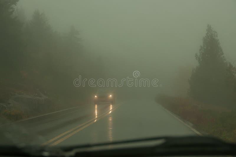 Widok od przedniej szyby samochód na drodze w silnej mgle i reflektorach nadchodzący samochód Droga jest w zmroku da obrazy royalty free