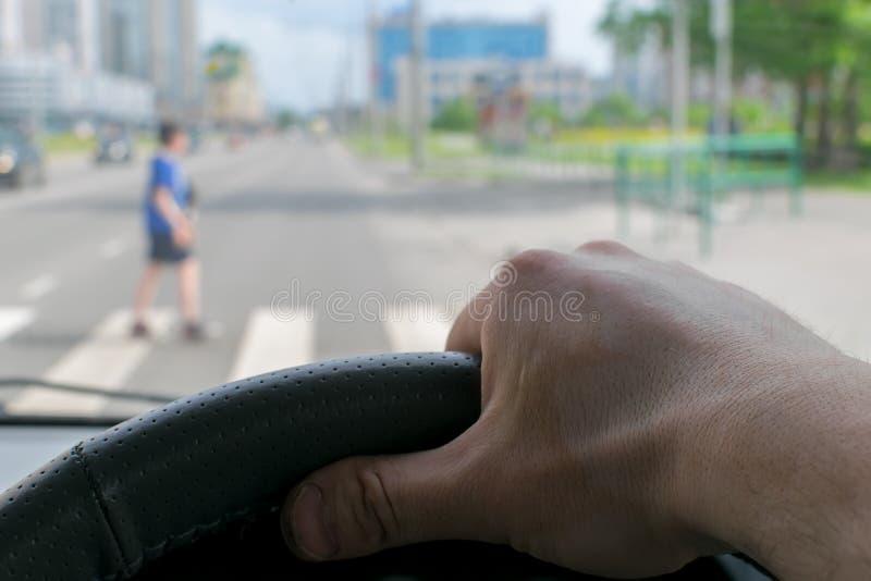 Widok od samochodu m??czyzna r?ka na kierownicie samoch?d, lokalizowa? naprzeciw zwyczajnego skrzy?owania zdjęcia royalty free