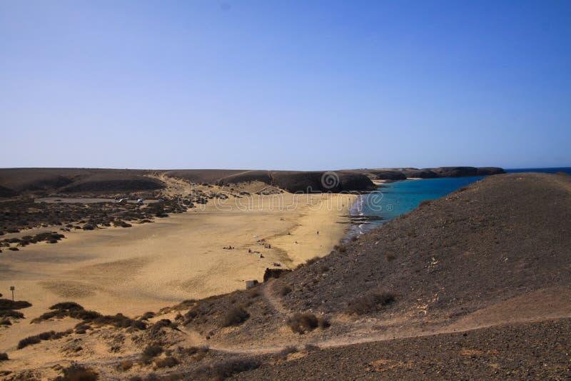 Widok od wzgórza na szerokiej plaży z świetnym piaskiem - Playa Mujeres, Playa Blanca, Lanzarote obraz stock