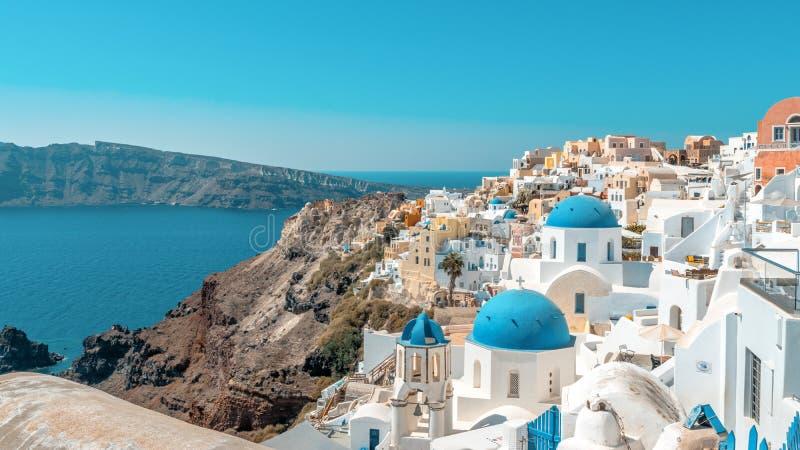 Widok Oia miasteczko z domami i kościół z błękitnymi kopułami nad kalderą na Santorini wyspie tradycyjnymi i sławnymi Grecja obraz stock