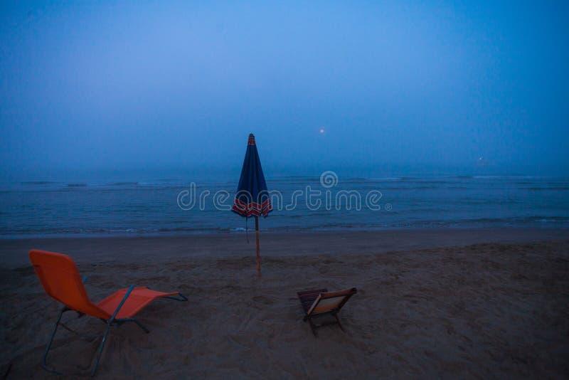 Widok parasol i dwa deckchairs na plaży podczas niezwykłego lata mgłowego ranku zdjęcia stock