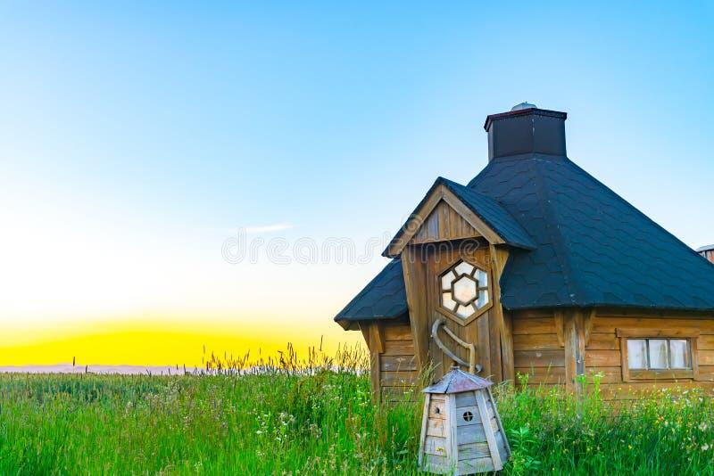 Widok piękna drewniana buda na prostym dzikiej trawy polu z zmierzchem zaświeca na tle zdjęcie royalty free