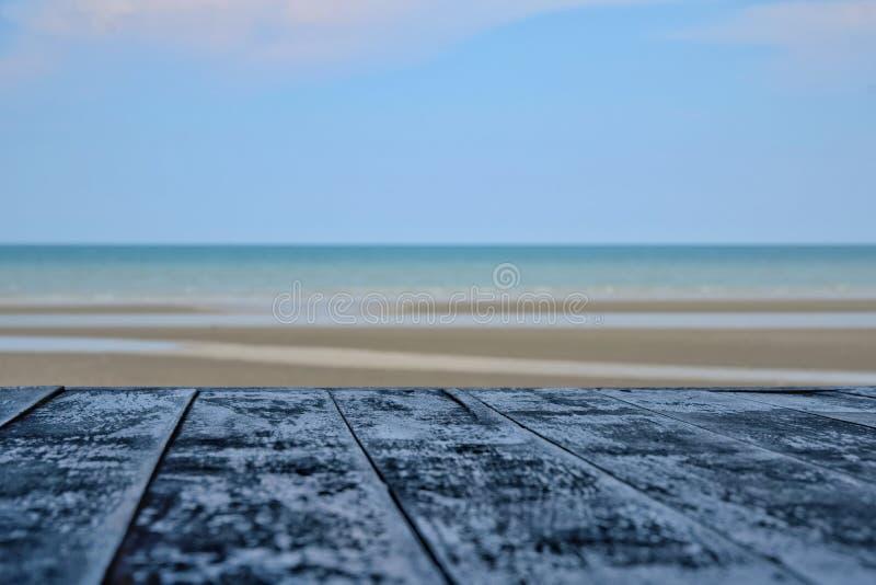 Widok piasek plaża, morze i niebieskie niebo z drewnianym stołem zdjęcie royalty free