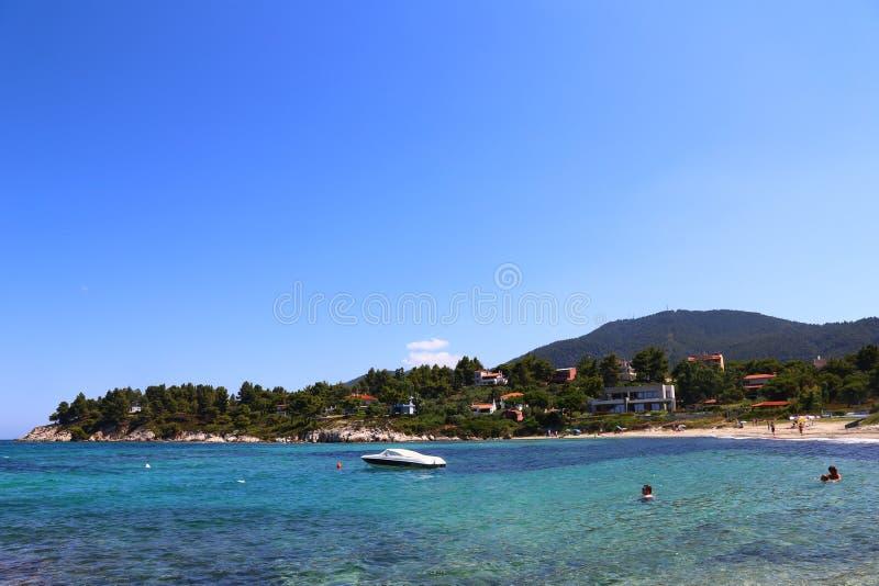 Widok plaża z ludźmi i łodzią na wodnym sithonia Greece zdjęcia stock