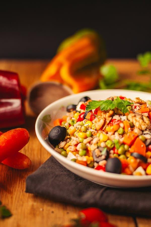 Widok przeliterowany naczynie na drewnianym tle z niekt?re sk?adnikami woko?o: marchewki, pieprze, pomidory, pietruszka i olej, zdjęcia stock