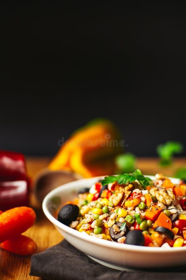 Widok przeliterowany naczynie na drewnianym tle z niekt?re sk?adnikami woko?o: marchewki, pieprze, pomidory, pietruszka i olej, zdjęcia royalty free