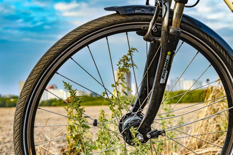 Widok przez frontowego koła bicykl W tle ty możesz widzieć pole i unfocussed satelitarnego miasteczko Gropiusstadt obraz stock