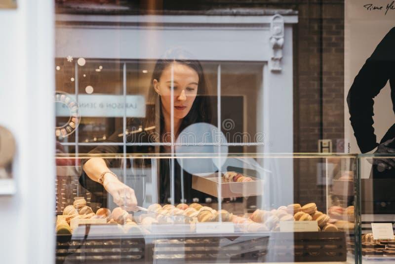 Widok przez okno kobiety kładzenia macaroons w pudełku wśrodku rzemieślnik piekarni w Covent Garden, Londyn, UK zdjęcia stock