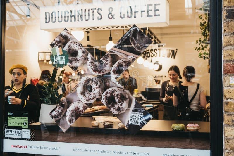 Widok przez okno ludzie wśrodku Crosstown pączków i kawowej kawiarni w Greenwich rynku, Londyn, UK zdjęcie stock