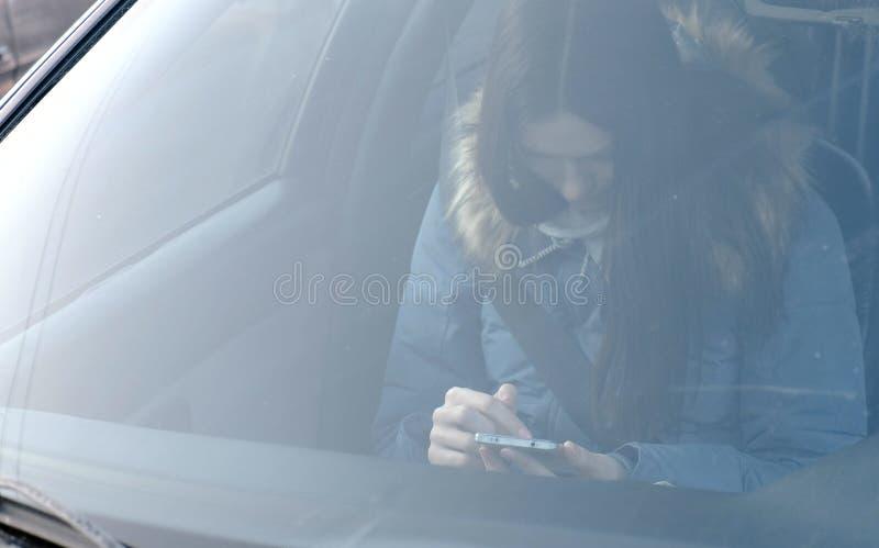 Widok przez przedniej szyby samochód na młodej brunetki kobiecie patrzeje telefon w błękita puszka kurtce obrazy stock