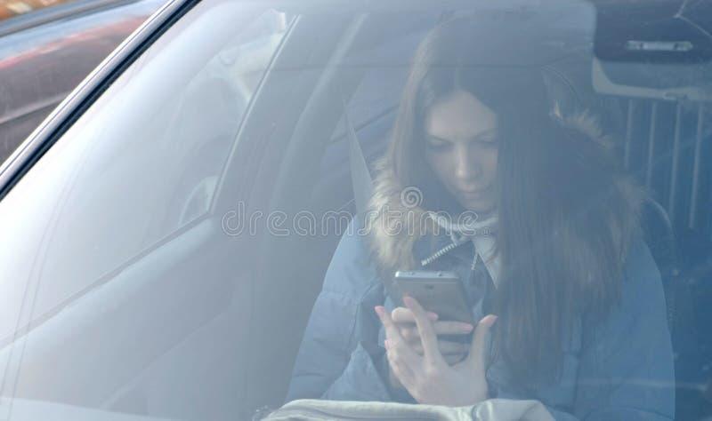 Widok przez przedniej szyby samochód na młodej brunetki kobiecie patrzeje telefon w błękita puszka kurtce obraz stock