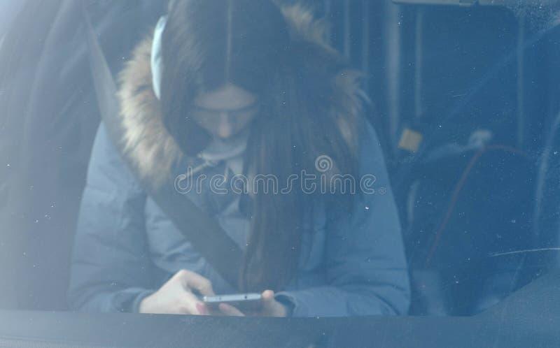 Widok przez przedniej szyby samochód na młodej brunetki kobiecie patrzeje telefon w błękita puszka kurtce obrazy royalty free