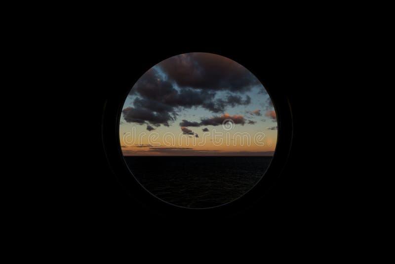 Widok przez round porthole zatapia na świcie przy morzem obrazy royalty free
